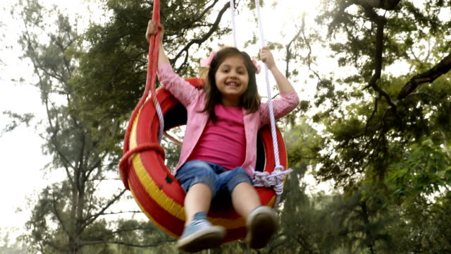 ms girl swinging on tyre swing in garden / delhi, india - tyre swing stock videos & royalty-free footage