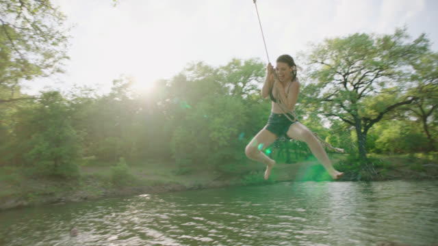 stockvideo's en b-roll-footage met ws slo mo. girl swings over river with rope and splashes into the water as friends cheer her on. - vrijheid