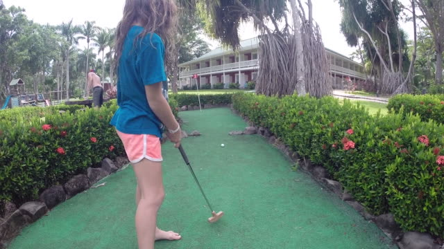 girl takes a shot at her golf ball on mini golf course with father in background at a resort. - kelly mason videos 個影片檔及 b 捲影像