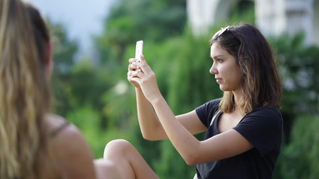 mädchen nimmt foto mit smartphone sitzen neben freundin - mittellanges haar stock-videos und b-roll-filmmaterial