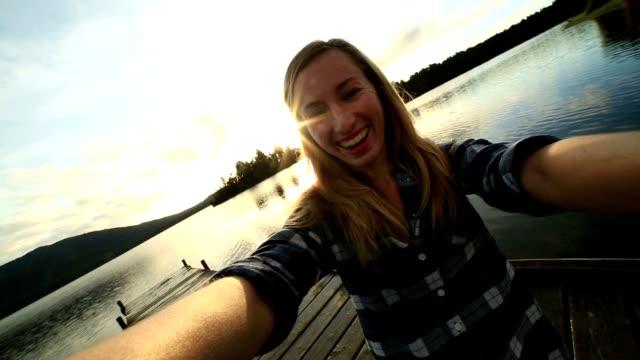 Mädchen nimmt Selfie auf See pier