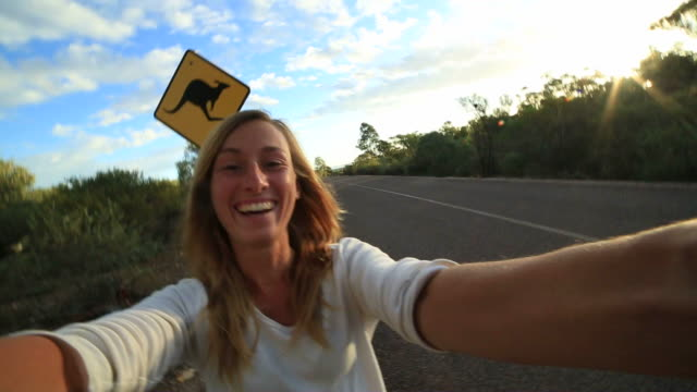 girl takes selfie portrait with kangaroo warning sign - road warning sign stock videos & royalty-free footage