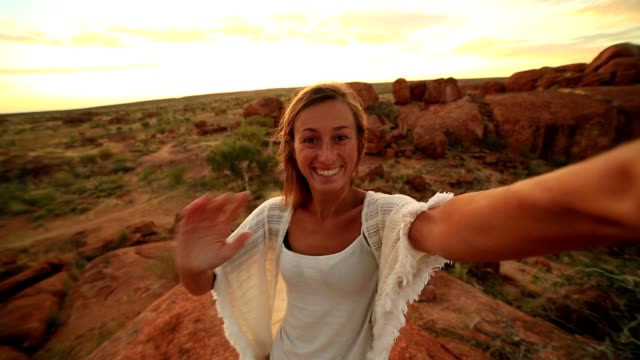 Girl takes selfie portrait with spectacular landscape at sunrise