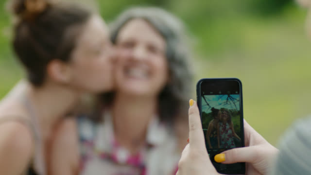 vídeos de stock e filmes b-roll de ms. girl takes smartphone photo of sister kissing mom and shares it with them at treetop overlook. - mulheres maduras