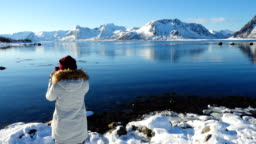 girl taking a photo of sunny winter fjord at Lofoten archipelago at the nothern Norway with her smartphone