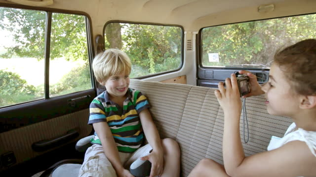 girl taking a photograph of her brother pulling faces in car - digital camera stock videos & royalty-free footage