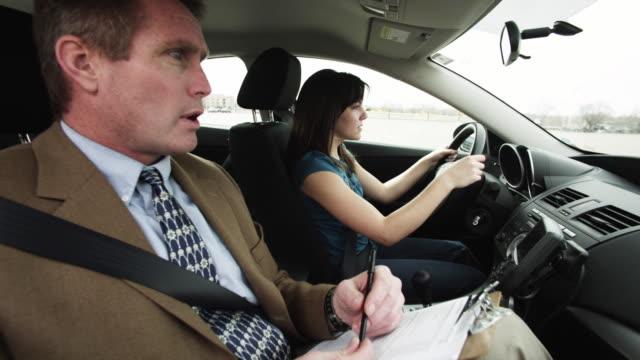 vídeos de stock, filmes e b-roll de ms girl (16-17) taking driving test, instructor grabbing steering wheel / orem, utah, usa - orem utah