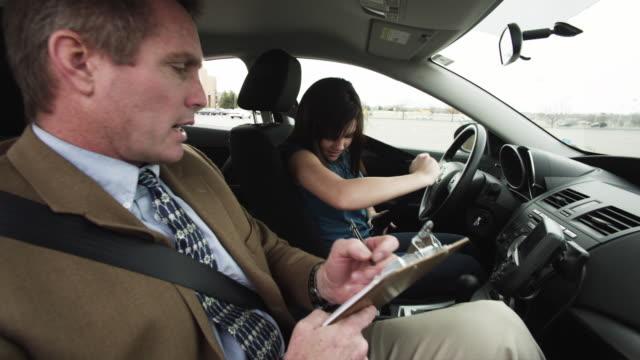vídeos de stock, filmes e b-roll de ms girl (16-17) taking driving test, instructor writing in clipboard / orem, utah, usa - orem