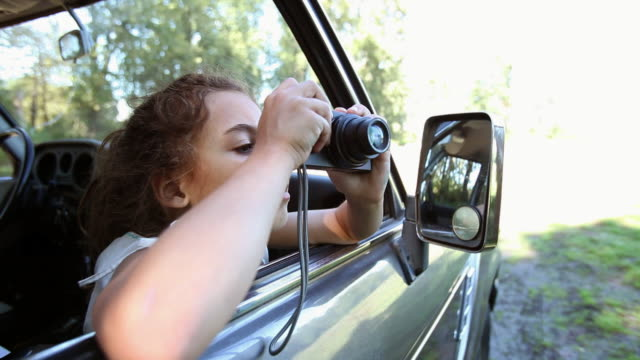 girl taking pictures from window of automobile - 撮影テーマ点の映像素材/bロール