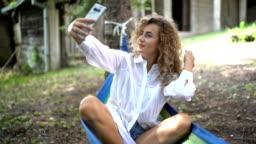 Girl taking selfie in hammock