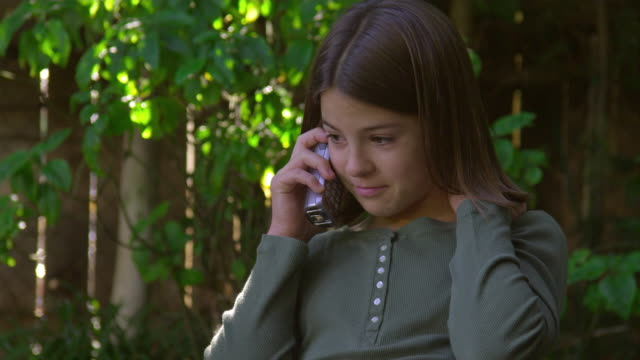 cu, girl (10-11) talking on mobile phone in garden, hollywood, california, usa - 10 11 jahre stock-videos und b-roll-filmmaterial
