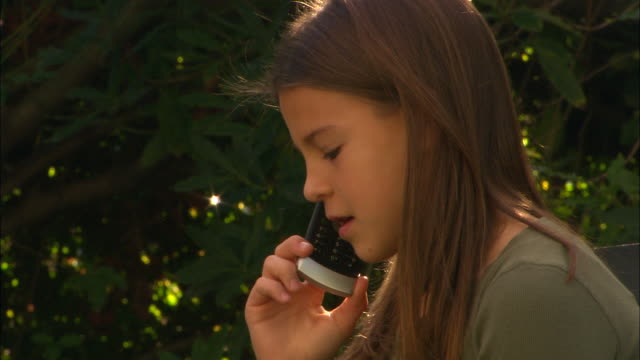 CU, Girl (10-11) talking on mobile phone in garden, Los Angeles, California, USA