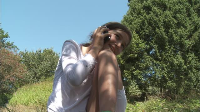 vídeos y material grabado en eventos de stock de ms girl (10-11) talking on mobile phone on meadow, bouillon, belgium - encuadre de tres cuartos