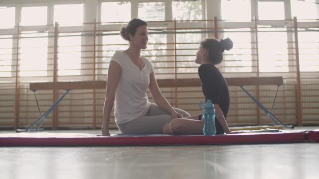 stockvideo's en b-roll-footage met 4k: meisje praten met haar coach turnen. - trainer