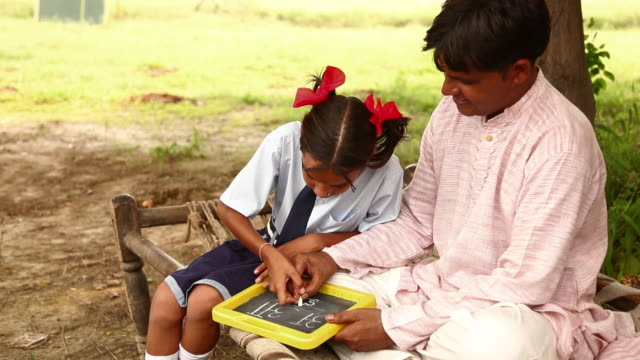 girl teaching to her father, haryana, india - slate rock stock videos and b-roll footage