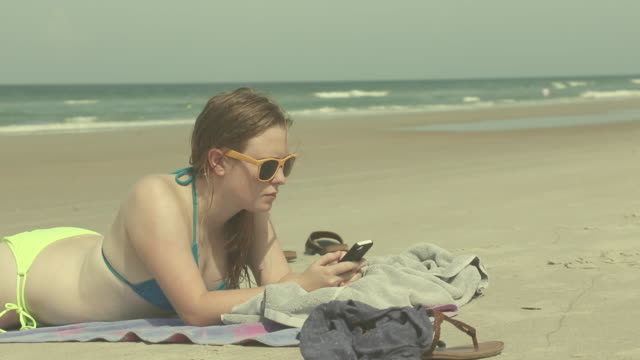 girl texting at the beach - asciugamano video stock e b–roll