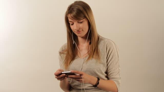 vídeos y material grabado en eventos de stock de girl texting on her cellphone - sólo una adolescente