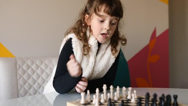 チェスゲームで彼女の次の動きを考えている女の子 - dia点の映像素材/bロール