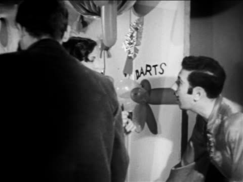 vidéos et rushes de b/w 1949 girl throwing dart at something offscreen / educational - couple d'adolescents