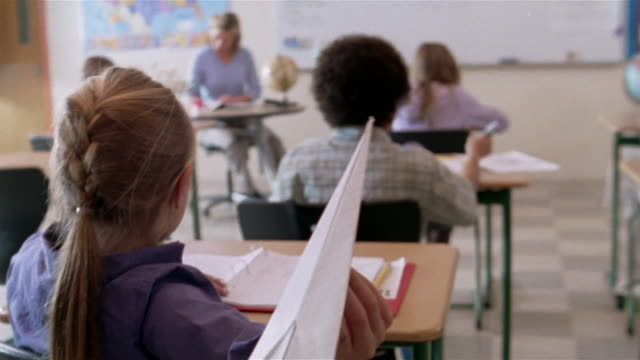 Girl throwing paper airplane in class / teacher looking up from front of class in background / Gorham, Maine