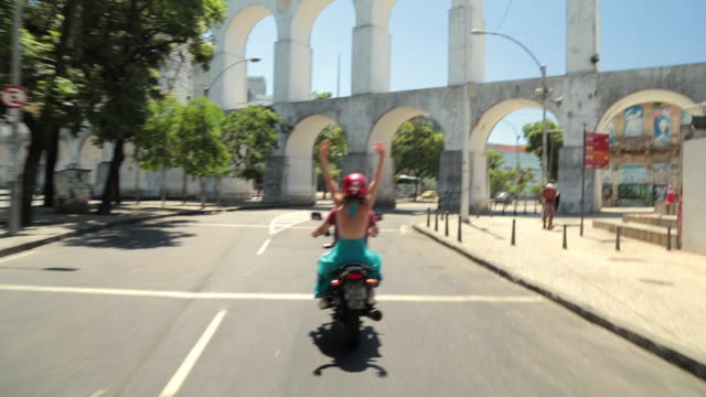 girl throws hands in the air and cheers as mototaxi drives under rio's famous arcos da lapa - サンドレス点の映像素材/bロール