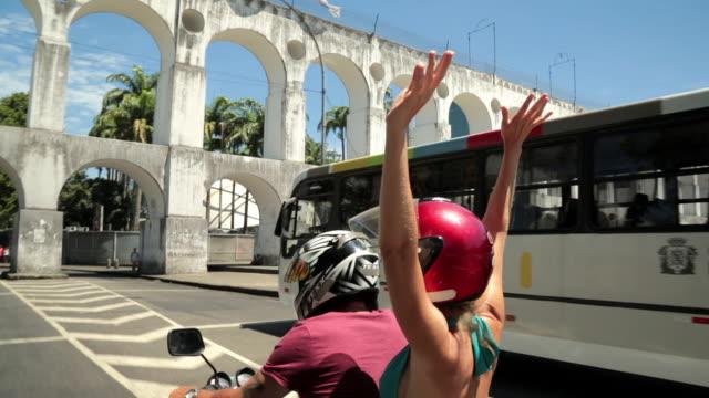 vídeos de stock, filmes e b-roll de girl throws hands in the air and cheers as mototaxi drives under the lapa arches - de braço levantado