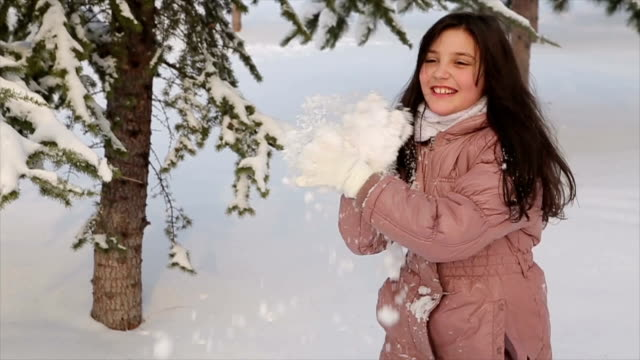 Girl throws into someone a snowball.
