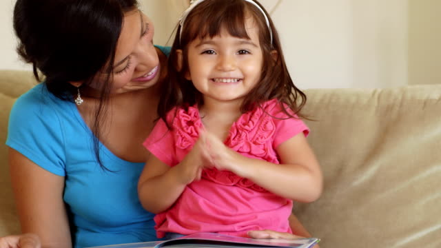Girl Toddler Giggling While Mother Reads to Her