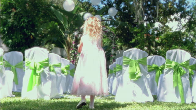ws girl (8-9) tossing rose petals before wedding, another girl and boy running around / tampa, florida, usa - blütenblatt stock-videos und b-roll-filmmaterial