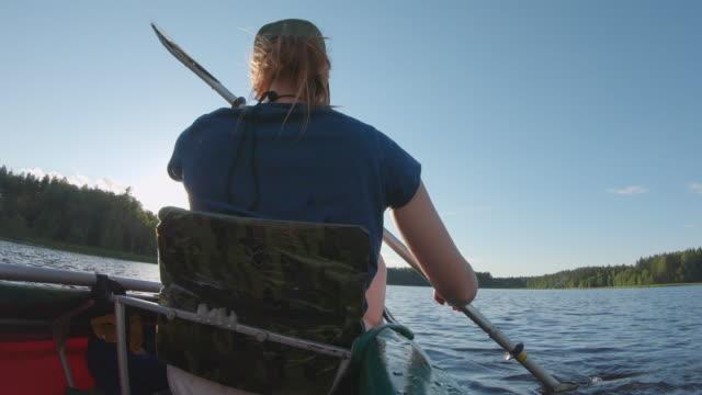 女の子の旅行者は湖でカヤックで泳ぐ - 人の背中点の映像素材/bロール