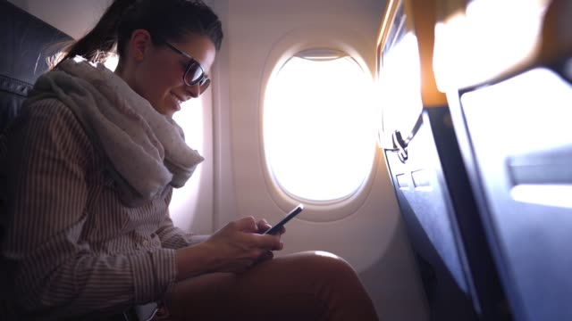 girl traveling by plane and using mobile phone - comfortable stock videos & royalty-free footage