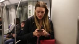 girl  traveling in metro car and using mobile phone