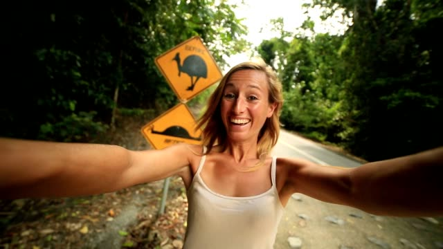 girl traveling takes selfie with humorous cassowary road sign - direction stock videos & royalty-free footage