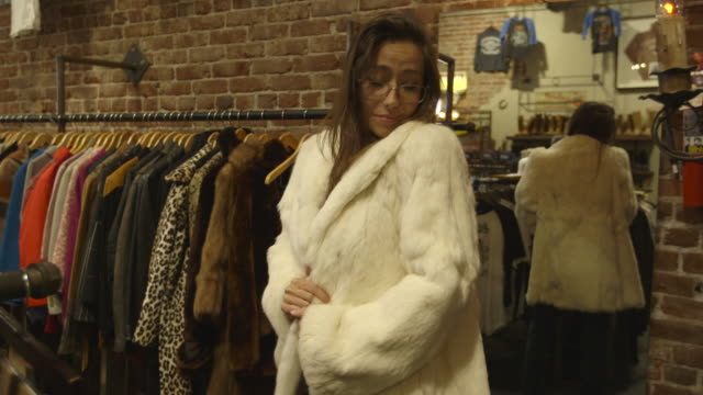 stockvideo's en b-roll-footage met girl tries on fur coat in vintage clothing store - dragen