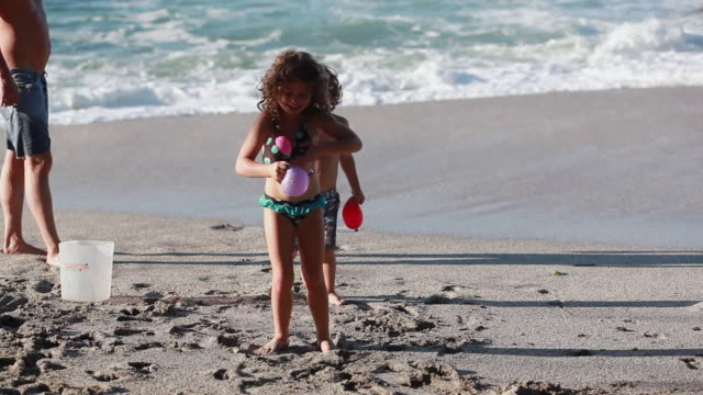 vídeos de stock, filmes e b-roll de ms ts girl tries to put two water balloons in bikini and boy steals one away to hold up to his chest as they fight over one water balloon on beach with ocean and man / montezuma, puntarenas, costa rica - kelly mason videos