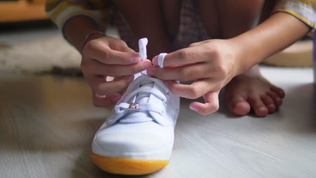 vídeos de stock, filmes e b-roll de garota tenta amarrar sapatos brancos, câmera lenta. - amarrar