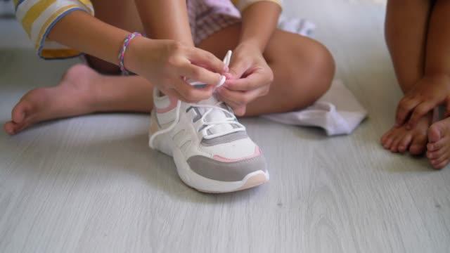 vídeos de stock, filmes e b-roll de garota tenta amarrar sapatos brancos, câmera lenta. - sapato