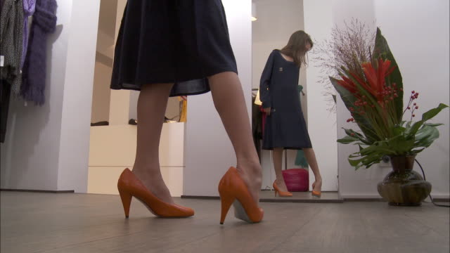 MS Girl (10-11) trying on too big high heel shoes in fitting room / Brussels, Belgium
