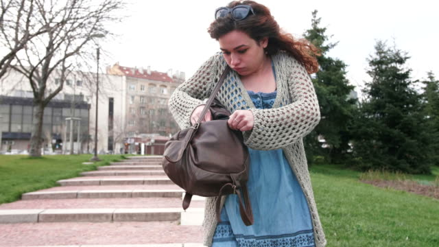 girl trying to find her mobile phone in her backpack and answering a call - borsetta video stock e b–roll