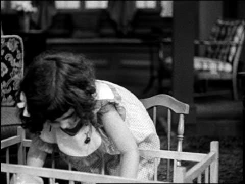 b/w 1948 girl tucking doll into crib / michigan / medical industrial - ドール点の映像素材/bロール