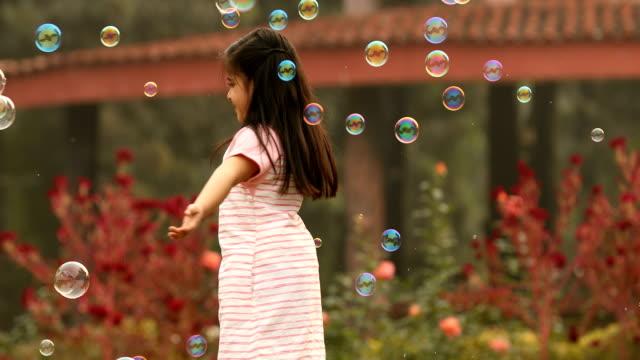 ms girl turning and playing with bubbles in park / india - endast flickor bildbanksvideor och videomaterial från bakom kulisserna