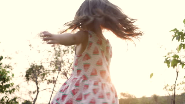 girl twirling at park in sunset - innocenza video stock e b–roll