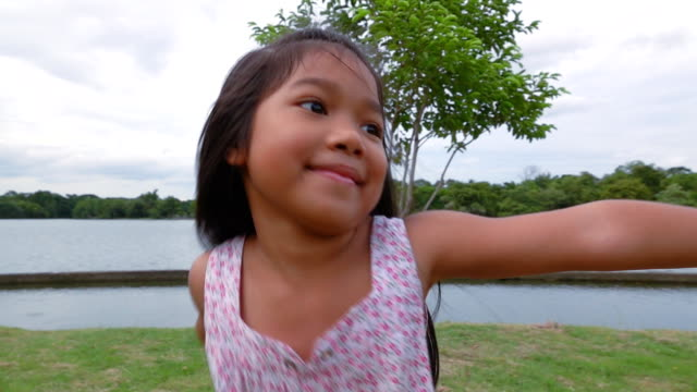 girl twirling on the green park, slow motion - children only stock videos & royalty-free footage