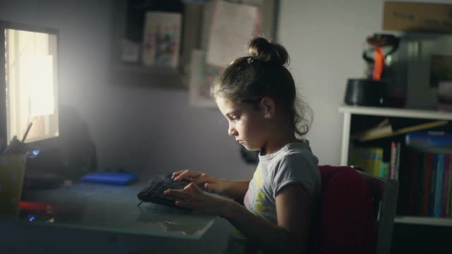 girl typing on computer keyboard - studio camera video stock e b–roll