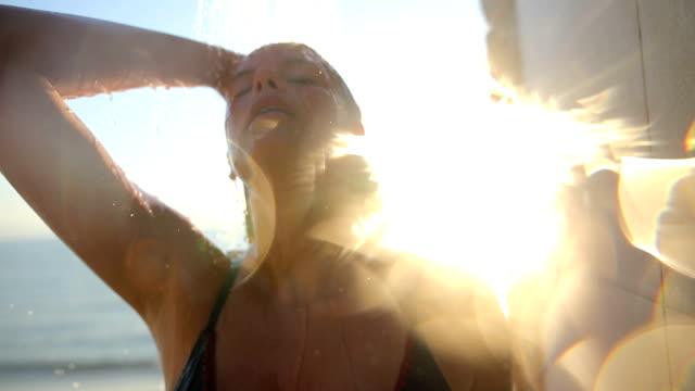 Chica en la ducha en la puesta de sol. Islas griegas