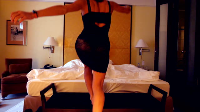 girl undresses for her partner in front of a bed in an hotel room - removing stock videos & royalty-free footage