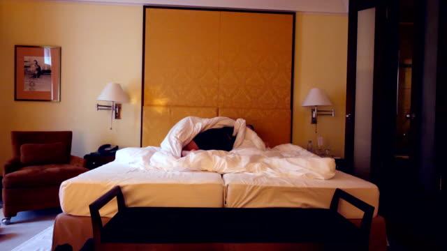 stockvideo's en b-roll-footage met meisje undresses voor haar partner voor een bed in een hotelkamer - seksuele thema's
