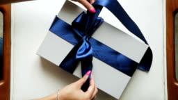 girl unties the ribbon on blue striped box