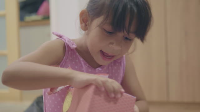 girl unwrapping a birthday present - unwrapping stock videos & royalty-free footage