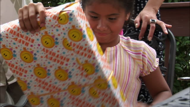 girl unwrapping gift at birthday party / new jersey - birthday gift stock videos & royalty-free footage